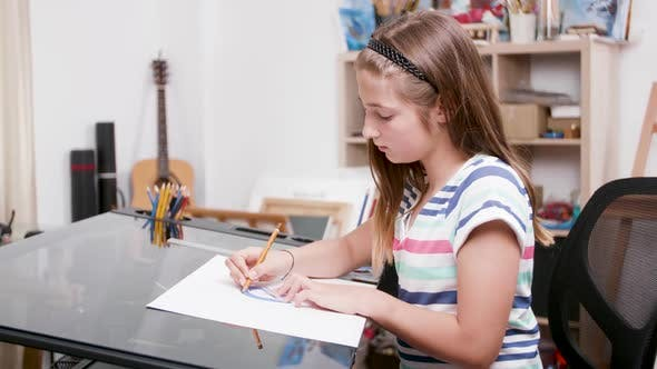 Young Girl Draws Some Lines Using a Pencil and a Protractor