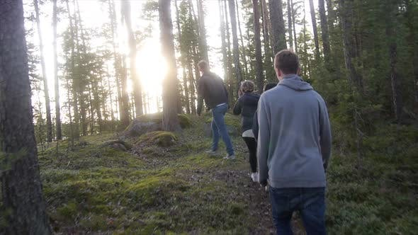 Young adults hiking through a forest near a lake.