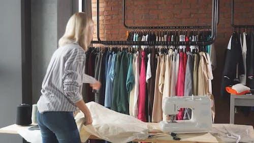 Young Female Fashion Designer Cutting a White Fabric