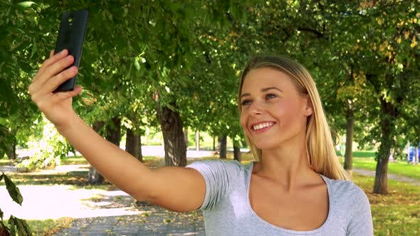 Thumbnail for Young Pretty Blond Woman Photographs with Smartphone (Selfie) - Park with Trees in Background