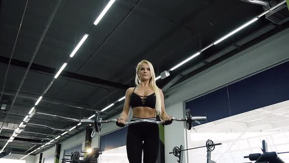 Attractive Sport Woman Making Exercises for Biceps with Barbells in the Gym