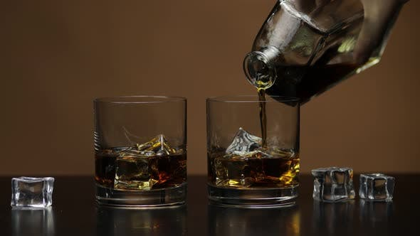 Pouring Whiskey, Cognac Into Glass. Brown Background. Pour of Alcohol Drink