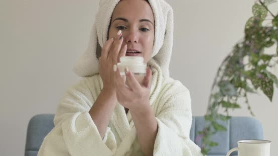Thumbnail for Portrait of a Young Caucasian Girl in White Bathrobe and Hair Towel Applying Face Cream