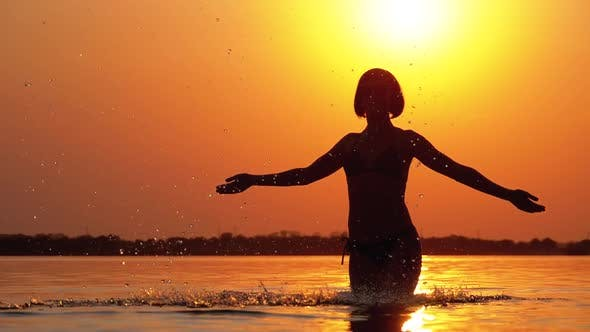 Thumbnail for Silhouette of Woman at Sunset Raises Hands Up and Creating Splashes of Water. Slow Motion