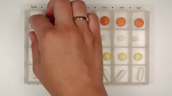Thumbnail for Female hand takes a pill from a pill organizer