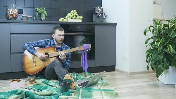 Thumbnail for Young hipster man learning to play chords on acoustic guitar and watching online video courses.