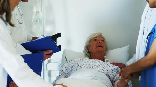 Group of doctors relieving old woman