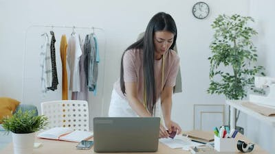 Young Asian Woman Fashion Designer Working with Laptop and Choosing Material for Handmade Garments