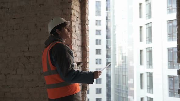 Thumbnail for Design Engineer at a Construction Site Looking at the Construction Drawings