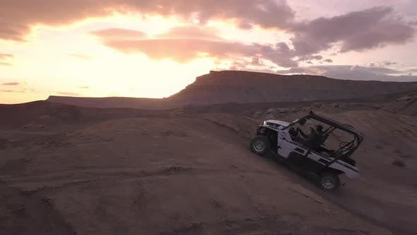 Thumbnail for Aerial panning view of OHV driving over dirt hill in the desert