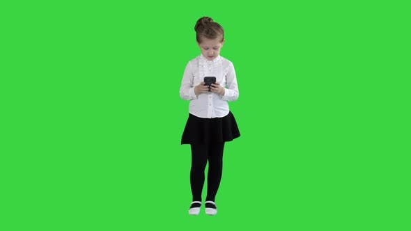 Cute Little Girl Looks in Smartphone and Writing a Message on a Green Screen, Chroma Key.