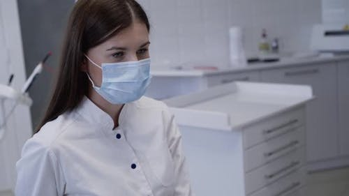 Confident Look of Dentist in Medical Mask Consulting Patient in Clinic