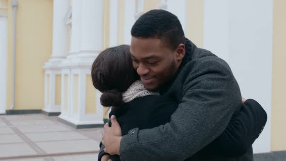 Thumbnail for Happy African American Man and Woman Hugging Meeting Unexpectedly Outdoors Slow Motion