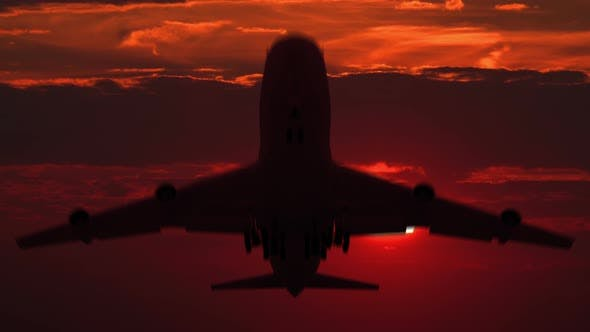 Cover Image for Large Airplane Silhouette Taking off against Red Sunset