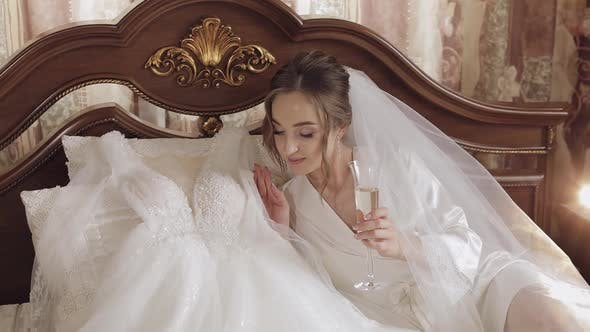 Thumbnail for Beautiful and Lovely Bride in Night Gown and Veil Sitting and Drinking Champagne