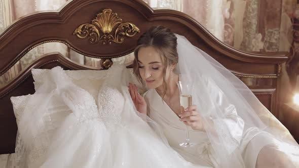 Thumbnail for Schöne und schöne Braut in Nacht Kleid und Schleier sitzen und trinken Champagner