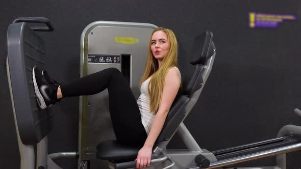 Thumbnail for A Young Beautiful Woman Trains on a Leg Press Machine in a Gym - View From the Side