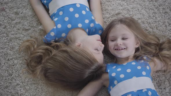 Cover Image for Top View of Two Pretty Caucasian Twin Sisters Lying on Soft Carpet and Smiling. Camera Moving Around