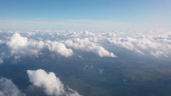 Thumbnail for Beautiful Aerial View at Land and White Fluffy Clouds Through Window of Flying Plane.