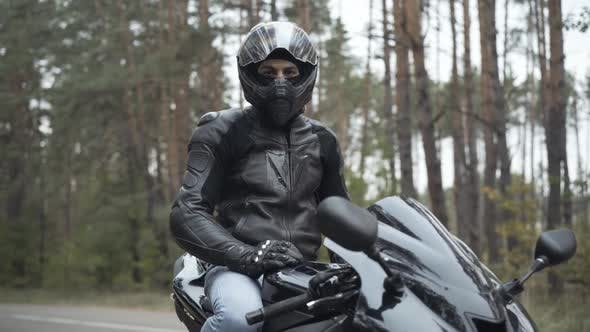 Portrait of Handsome Confident Middle Eastern Man in Helmet Sitting on Motorbike and Looking at