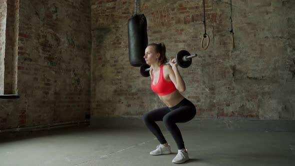 Junge Frau macht Kniebeugen-Übungen
