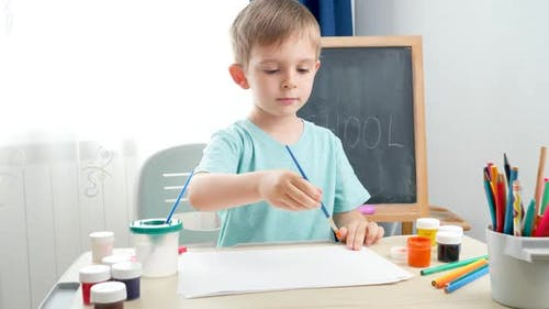 Little Boy Drawing Picture with Guache Paint