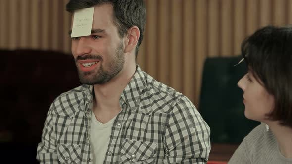 Thumbnail for Young Beautiful People at Cafe Table Playing Name Game with Sticker Notes Sticked To Their Forehead