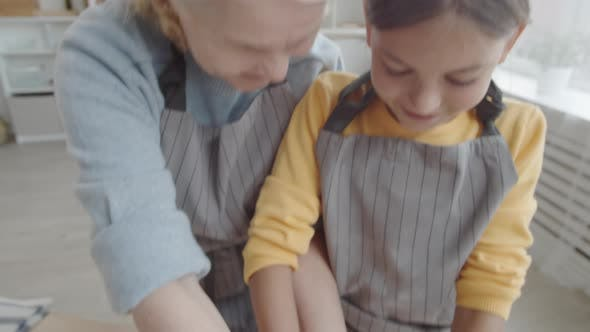 Thumbnail for Grandmother and Granddaughter Making Dough Together at Kitchen Table