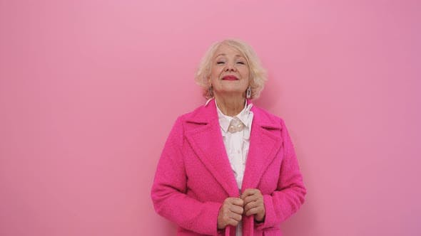 Pretty Aged Lady Dressed in a Stylish Pink Coat with Healthy Fresh Skin Poses in a Studio