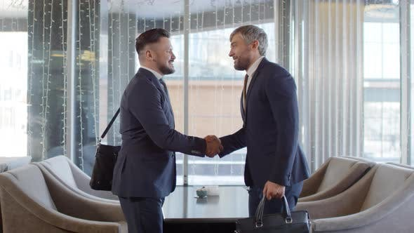 Thumbnail for Two Businessmen Greeting Each Other in Café