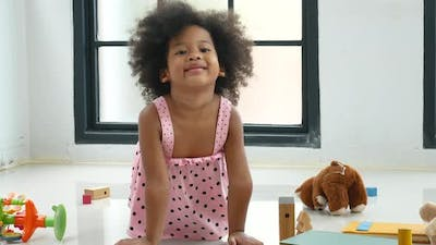 African American little girl play toys alone and look at camera during play in living room