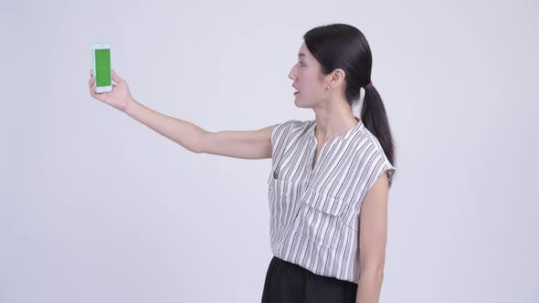 Cover Image for Happy Beautiful Asian Businesswoman Video Calling and Showing Phone