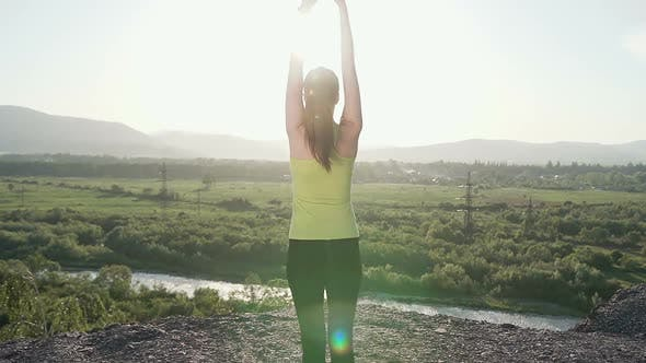 Cover Image for Young Sporty Woman Practicing Yoga on the Top of Mountain at Sunset