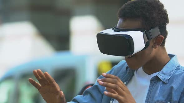 Excited African-American teen boy using VR headset, modern technology