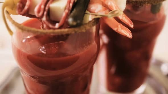 Thumbnail for Bloody mary cocktail garnished with celery sticks, olives, and bacon strips.
