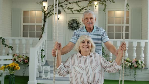 Thumbnail for Senior Couple Together in Front Yard at Home. Man Swinging and Hugging Woman. Happy Mature Family