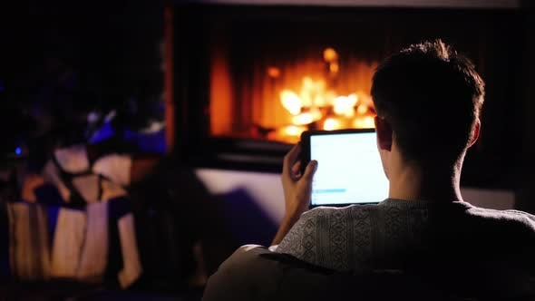 Cover Image for A Man Orders Gifts for Christmas, Sitting at Home By the Fireplace. Using Tablet