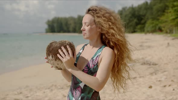 Thumbnail for Puzzled Female Shaking Coconut on Beach