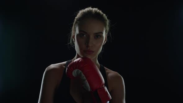 Thumbnail for Junge Frau posiert mit roten Boxhandschuhe auf schwarzem Hintergrund im Studio