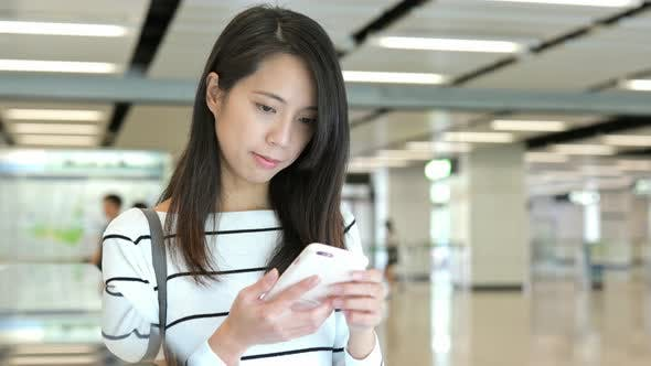 Thumbnail for Young Woman working on cellphone in station hall