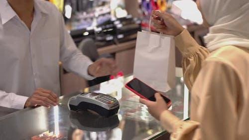 Asian Muslim Woman Using Mobile Phone Paymen
