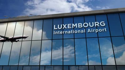 Airplane landing at Luxembourg airport mirrored in terminal