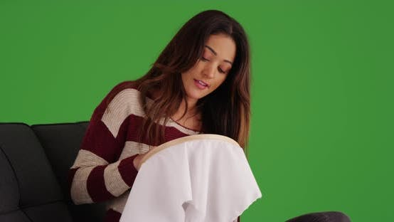 Thumbnail for Woman relaxing in living room, embroidering fabric on green screen