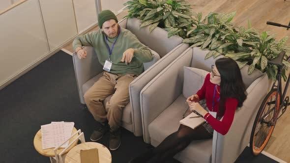Draufsicht auf junge Geschäftsleute beim Chatten
