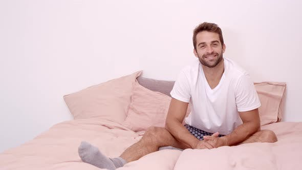 Smiling Guy Sitting On Bed