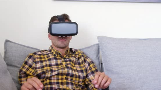 Young man using virtual reality headset in living room at home