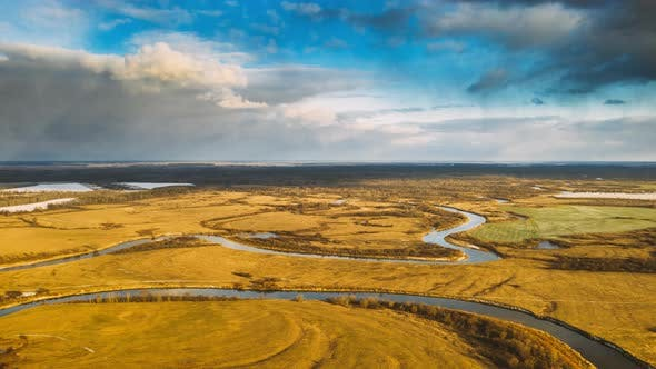 Aerial View Of Dry Meadow And Partly Frozen River Landscape In Sunny Autunn Day. Top View Of