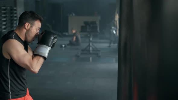 Aggressiver Profi-Kämpfer trainiert mit einem Boxsack und verursacht einen wütenden Schlag.  Die