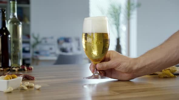 Hand Putting Glass Of Beer On Table