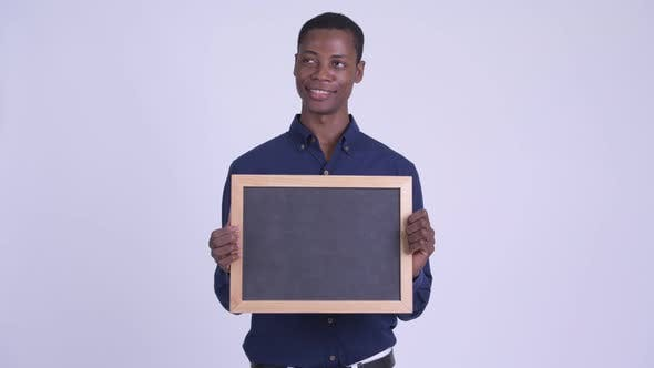 Young Happy African Businessman Holding Blackboard